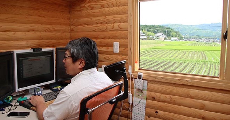 自宅の「オフィス」で仕事に励む丸井さん。窓の外には特産の黒豆畑が広がる