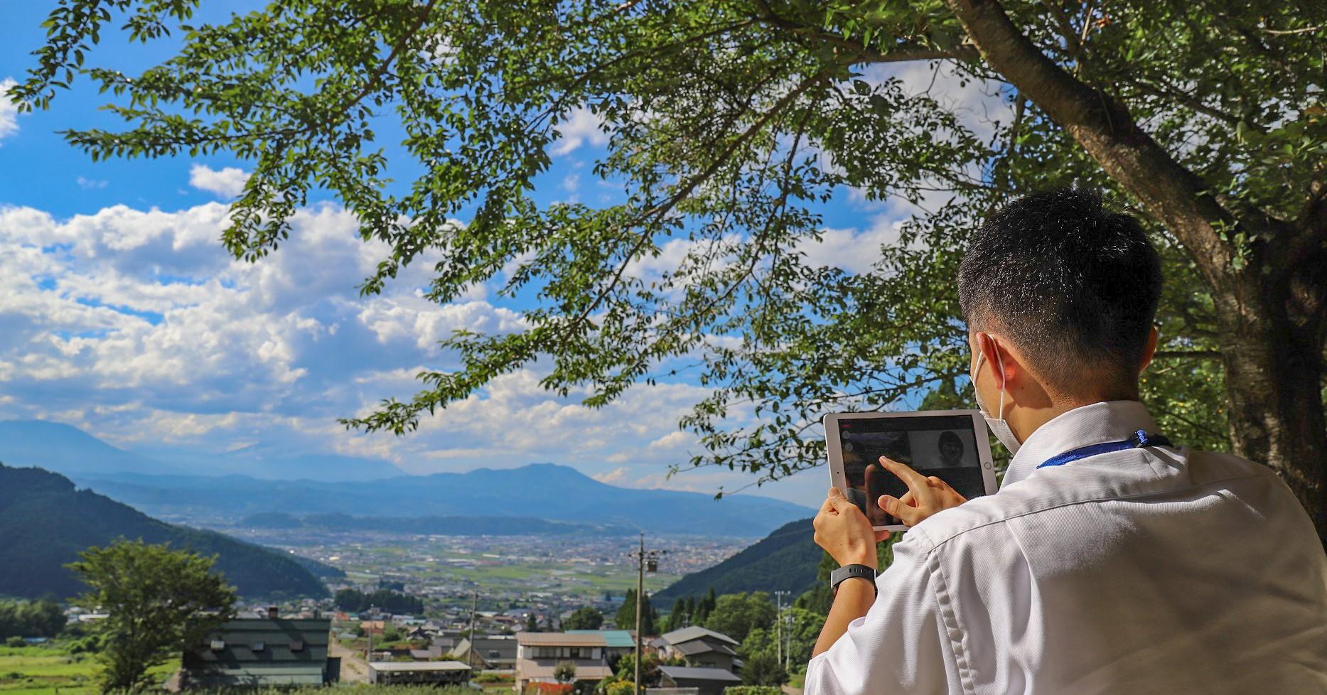 中野市街地が一望できる高台からタブレット越しにまちの紹介を行う様子